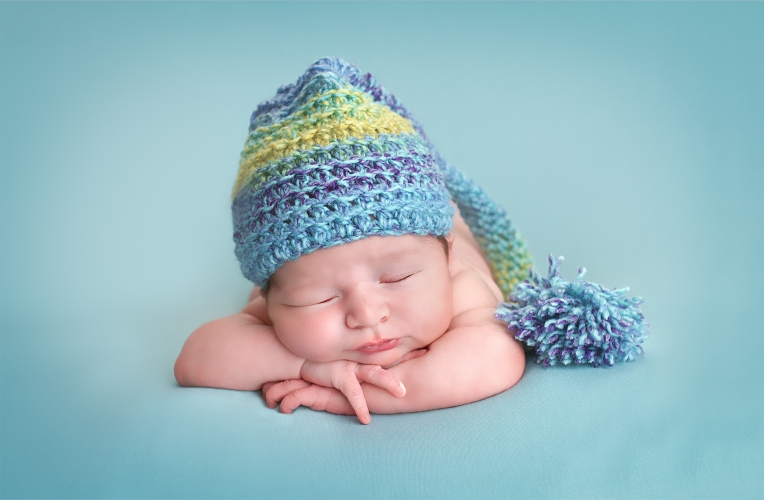 Sleeping Newborn wearing hat - Baby Whispers Photography Royston, Cambridge